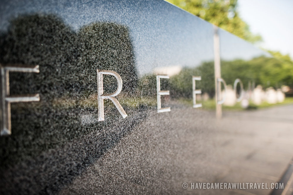"""Korean War Memorial Freedom. The word """"Freedom"""" is etched in to the granite wall of the Korean War Veterans Memorial. At the very right of frame, the lighter figures, out of focus, are reflections of the The Column of statues of soldiers that forms the centerpiece of the monument."""