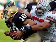 Defensive end Mike Kudla, right, sacks quarterback Brady Quinn of Notre Dame last night in the second quarter.
