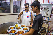 03 JULY 2014 - BANGKOK, THAILAND: Men serve chicken curry before Iftar, the meal that breaks the day long fast at Haroon Mosque in Bangkok during the holy month of Ramadan. Ramadan is the ninth month of the Islamic calendar, and the month in which Muslims believe the Quran was revealed. The month is spent by Muslims fasting during the daylight hours from dawn to sunset. Fasting during the month of Ramadan is one of the Five Pillars of Islam. Muslims believe that the Quran was sent down during this month, thus being prepared for gradual revelation by Jibraeel (Gabriel) to the prophet Muhammad.     PHOTO BY JACK KURTZ