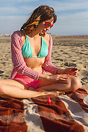 A young woman paints her nails while sunbathing.