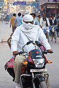 Man driving Hero Honda motorcycle with covered head and face in street scene in city of Varanasi, Benares, Northern India