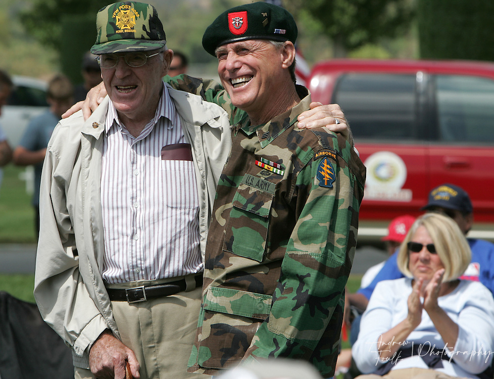 /Andrew Foulk/ For the Californian/.Ron McLaughlin, veteran of WWII and Korea, shares stories with David Karr Vietnam veteran and former Special Forces, as the T-34 Heritage Foundation performs the missing man flight over the Lake Elsinore cemetery, during the Memorial Day ceremony.