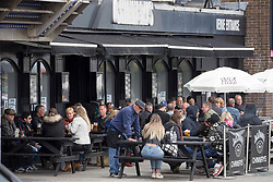 © Licensed to London News Pictures.  30/04/2021. Southend-on-Sea, UK. Member of the public enjoy their drink near Thames Estuary in Southend-on-Sea, Essex. Forecasts predict chilly bank holiday weekend with showers which may turn heavy at times during the afternoon, most likely near the south coast. Photo credit: Marcin Nowak/LNP