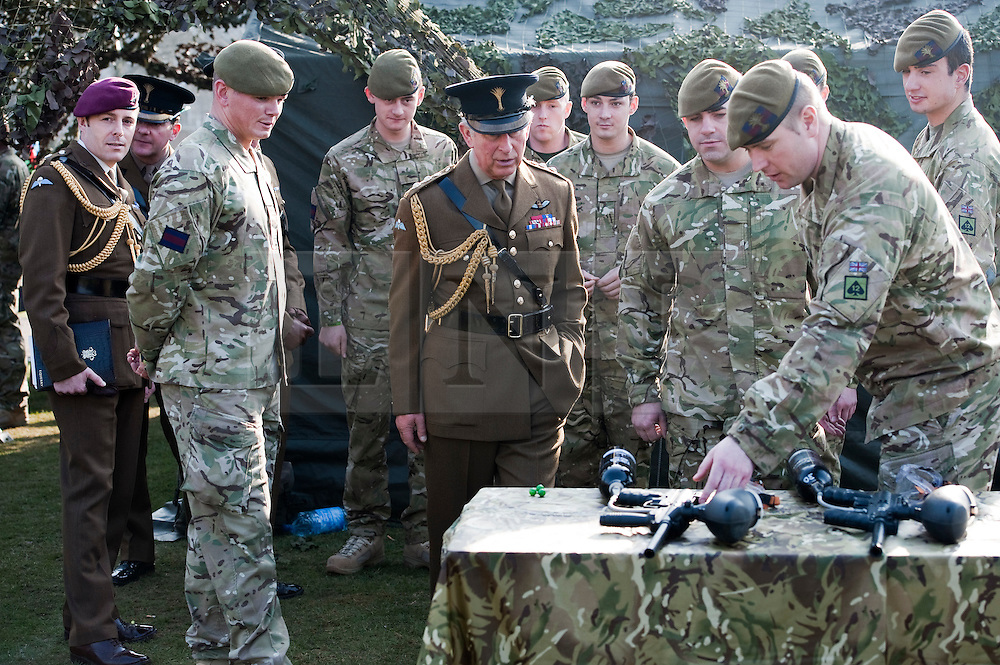 © Licensed to London News Pictures. 01/03/2012. Hounslow, UK.    Prince Charles, The Prince of Wales, being shown how to fire a paintball gun by The Prince of Wales Guards after Presenting leeks to 1st Battalion The Welsh Guards at Cavalry Barracks,  Hounslow, London on St David's Day, March 1st, 2012.  Two-thirds of the Battalion's 600 soldiers are due to be deployed to Afghanistan in the next two weeks. Photo credit : Ben Cawthra/LNP