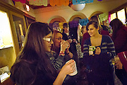 """Sofia Carpio Leon '12 and other students sip hot chocolate and mingle during the Day of the Dead gathering in Goodnow Hall, sponsored by Professor John Seebach and the Anthropology Department. The Day of the Dead (""""dia de los muertos"""") is a Mexican holiday to honor loved ones who have passed away."""