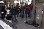 A woman street beggar prostrates herself on a pavement, ignored by Italian shoppers and pedestrians in Florence. As shoppers and tourists walk past in a hurry, pulling suitcases or carrying shopping, the people walk around the kneeling body whose stick lies on the ground with a paper cup to collect any spare change offered. There seems to be a mixture of indifference, pity and shame for what has become the modern face of Italian society in this once-grand medieval city. The city lies on the River Arno and is known for its history and its importance in the Middle Ages and in the Renaissance, especially for its art and architecture. A centre of medieval European trade and finance and one of the wealthiest cities of the time, Florence has been called the Athens of the Middle Ages.