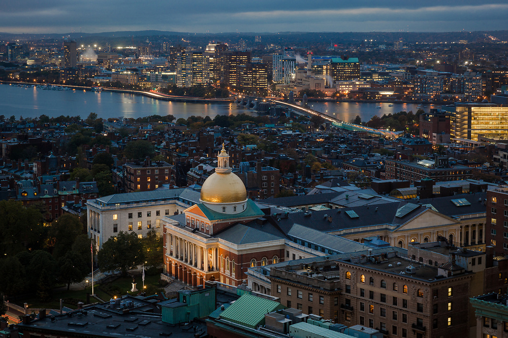 An evening view of the Massachusetts State House and Cambridge Skyline seen from a skyscraper in Downtown Boston.