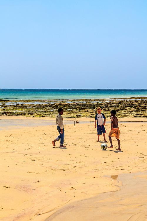 Children are playing football on Diani beach, Kenya.