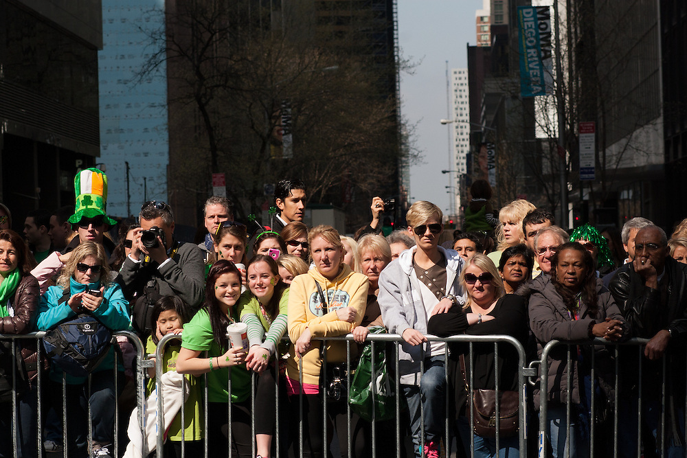 Throngs behind barricades beside the parade route.