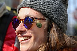© Licensed to London News Pictures. 15/04/2019. London, UK. A woman is seen with an Extinction Rebellion logo painted on her face as Environmental activists demonstrates in Oxford Circus to demand decisive action from the UK Government on the environmental crisis. Photo credit: Dinendra Haria/LNP