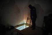 State police officer looks inside a tunnel that leads to an underground greenhouse at a ranch in Tecate, Mexico. SPANISH: Un policia estatal observa la entrada oculta a un sotano, donde se encontro un invernadero de marihuana en un rancho en Tecate, México. 11 de marzo de 2009.
