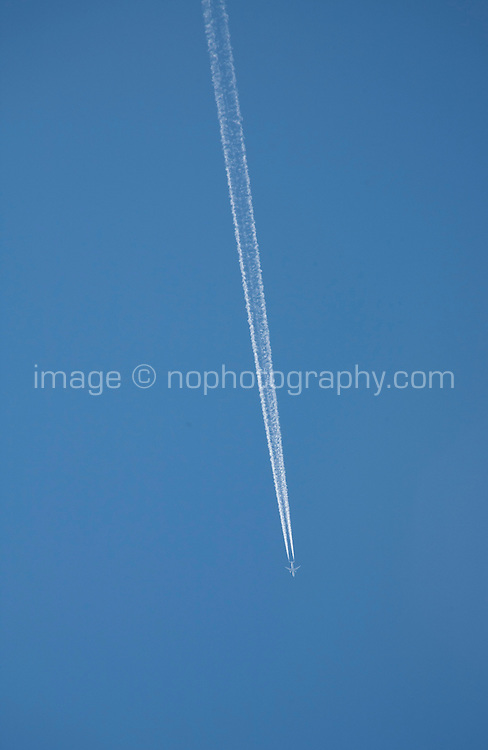 Airplane with vapour trails in the sky over Dublin Ireland