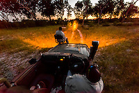 A tracker sits in a seat on the front of a safari vehicle and holds a spotlight looking for nocturnal animals on a night game drive, Kwara Camp, Okavango Delta, Botswana.