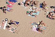 Nederland, Nijmegen, 25-6-2020 Mensen trekken massaal naar de oevers van de waal en de spiegelwaal in het rivierpark aan de overkant van Nijmegen . De warmte, hoge temperatuur, drijft mensen naar het water . Het is verboden in de rivier te zwemmen vanwege de stroming het het drukke scheepvaartverkeer .Foto: ANP/ Hollandse Hoogte/ Flip Franssen