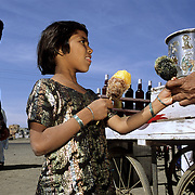 A young girl buying Gola on a hot summer day near Bhuj (gujarat). Gola (or Chuski) is the poor man's ice cream. It is basically crushed ice flavoured with colored syrup.