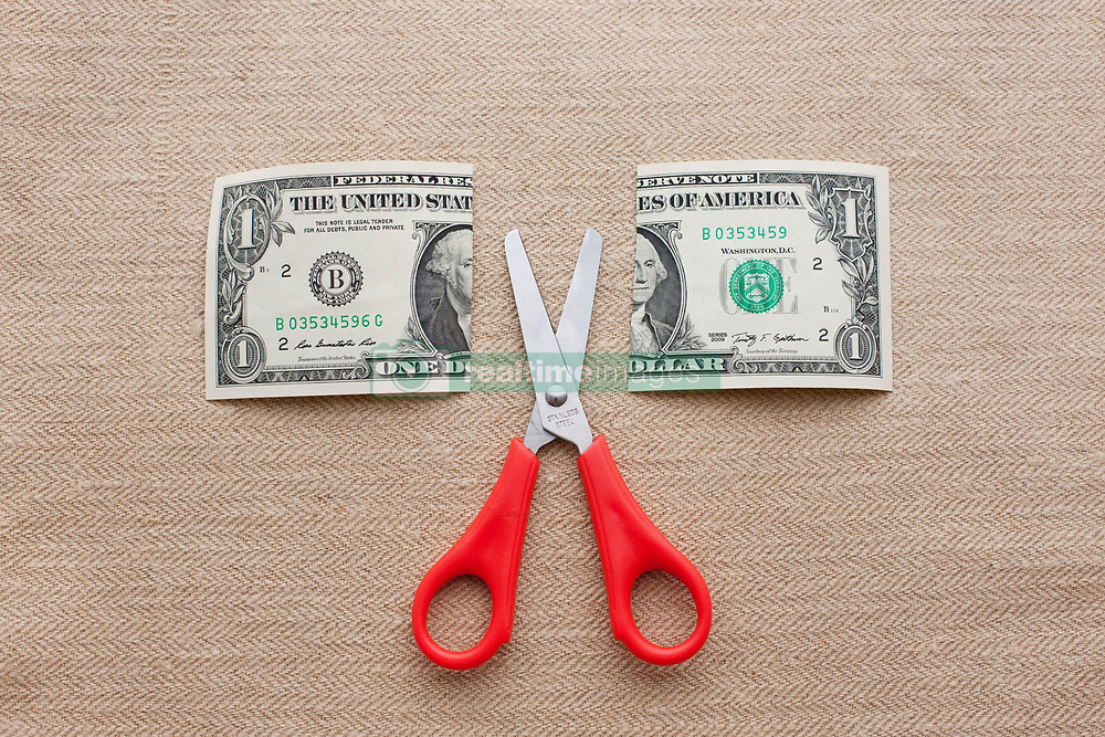 One dollar bill cut in half with scissors (Credit Image: © Image Source/Ian Nolan/Image Source/ZUMAPRESS.com)