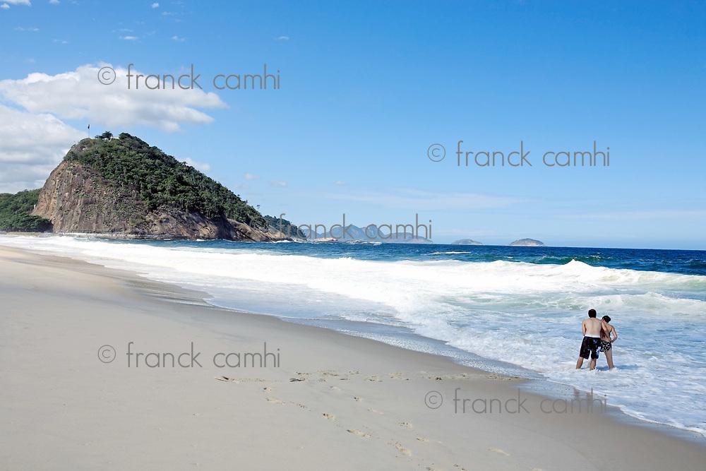 couple playing with the sea on copacabana beach in rio de janeiro in brazil