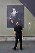 A man on the street reads about a portrait by Francesco Goya, sponsored by Credit Suisse and advertised on a construction hoarding outside the National Portrait Gallery. The portrait is of Bartolomé Sureda y Miserol and is owned by the National Gallery of Art in Washington DC. Standing awkwardly to echo the leaning stance of Goya's subject, the man reads the caption and other details of the artistic work, appreciating its beauty and informative descriptions. Paintings by the Spanish romantic court artist are being exhibited inside the National Gallery next door and while a large grey hoarding is in place during works in Trafalgar Square, some of Goya's work is reproduced to viewers outside.