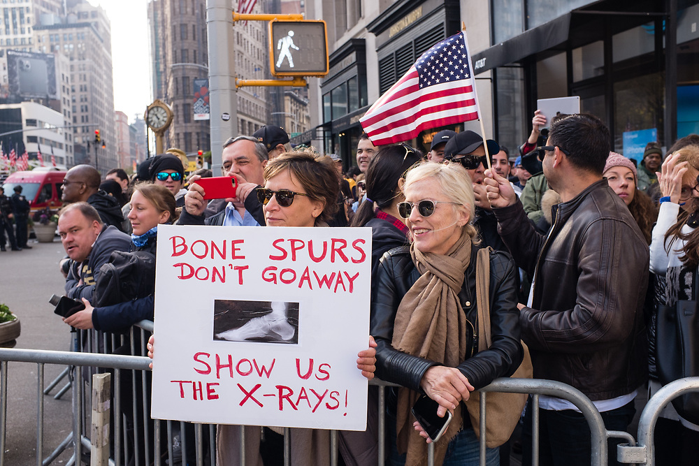 """New York, NY - 11 November 2019. New York City's Veterans Day Parade, today marking the 100th anniversary of the armistice ending the fighting of the first World War, was attended by a number of people protesting President Trump, who spoke at the opening ceremony, and a smaller number of pro-Trump supporters. A woman has a sign reading """"Bone Spurs don't go away / show us the x-rays."""""""
