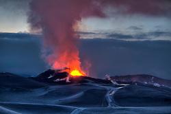 Volcanic eruption at Fimmvorduhals in Eyjafjallajokull. People traveling by jeeps and snowmobiles, Iceland - Eldgos á Fimmvörðuhálsi