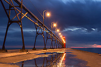 A water puddle that remains after a recent rain, reflects the South Haven lighthouse.