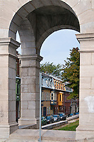 Looking through the arches at the back of the Presbytère St-Jean-Baptiste church in Quebec City reveals colorful row houses beyond.