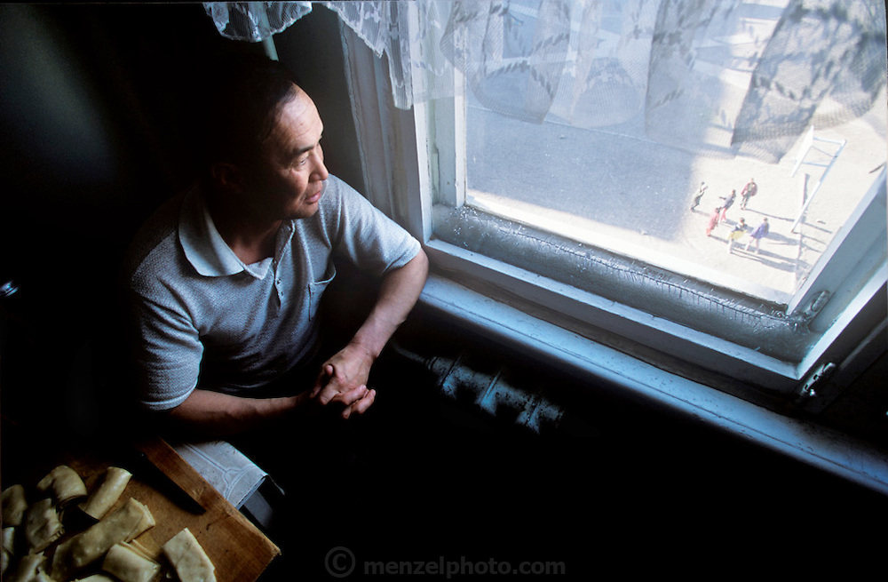 (MODEL RELEASED IMAGE). Regzen Batsuuri finds a contemplative moment during dinner preparations. (Supporting image from the project Hungry Planet: What the World Eats.) The Batsuuri family of Ulaanbaatar, Mongolia, is one of the thirty families featured, with a weeks' worth of food, in the book Hungry Planet: What the World Eats.