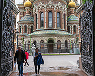 St Petersburg, Russia -- July 20, 2019.  A couple walks through an exit gate toward Alexander Garden. Church of the Spilled Blood is in the background.
