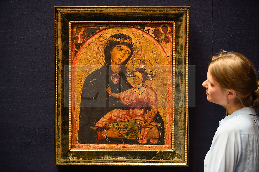 """© Licensed to London News Pictures. 28/06/2019. LONDON, UK. A staff member views """"The Madonna and Child, two angles in the spandrels above"""", mid 1230s, by Third Master of Anagni (Est. GBP200-300k) at the preview of Sotheby's Old Masters sale which takes place at its New Bond Street galleries on 3 July.  Photo credit: Stephen Chung/LNP"""