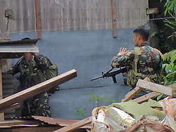 June 27, 2017 - Marawi City, Philippines - Government troops continuously doing house to house clearing operations in Marawi City. House based evacuees asking for more relief goods from NGOs and government as they go hungry. The streets of Marawi is heavily destroyed by bullets, mortar blasts and air strikes. Graffiti praising ISIS is written on walls. Fruits and vegetables in the market are all rotten because of the almost one month unrest in the Islamic City. (Credit Image: © Sherbien Dacalanio/Pacific Press via ZUMA Wire)
