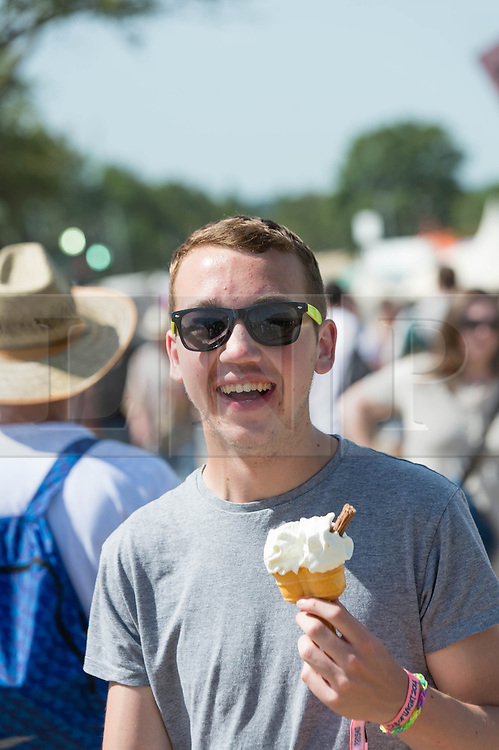 © Licensed to London News Pictures. 13/06/2014. Isle of Wight, UK.   A man enjoys a cooling ice cream in the hot sunny weather at the Isle of Wight Festival 2014.   Today is expected to be the hottest day of the year. The Isle of Wight festival is an annual music festival that takes place on the Isle of Wight. Photo credit : Richard Isaac/LNP