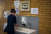 A school boy washes his hands on his way into class on his first day back in school after 4 weeks of coronavirus lock-down on April 17th 2020 in Aarhus  Denmark. All schools and much of Denmark including its borders were shut Monday March 16th by the Danish Prime Minister Mette Frederiksen to prevent the corona virus from spreading beyond control. All school children had to stay at home if possible during the lock-down and many had not seen their friends through-out the 4 weeks it lasted. All teaching was done at home and via online services such as Google Meet and to many time was difficult to pass. Only year 0-5 are now allowed back in school and only under special measures. Classes are split in twos and across two rooms, everyone must wash hands rigorously when they leave and enter the class and the children must observe distance when possible. The children are put together in groups of no more than three and they are the only ones they get to work  and play with. Break time has to be in designated areas only and only with class mates.