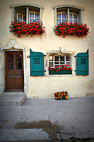 Photo of a facade with red flowers decorating the windows in Gruyere, Switzerland