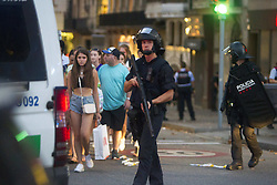 August 17, 2017 - Barcelona, Spain - People are escorted by Spanish policemen outside a cordoned off area after a van ploughed into the crowd, killing 13 persons and injuring over 80 on the Rambla in Barcelona on August 17, 2017. A driver deliberately rammed a van into a crowd on Barcelona's most popular street on August 17, 2017 killing at least 13 people before fleeing to a nearby bar, police said. Officers in Spain's second-largest city said the ramming on Las Ramblas was a 'terrorist attack' (Credit Image: © Hugo FernáNdez Alcaraz/NurPhoto via ZUMA Press)