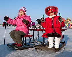 Two young girls playing on the frozen Songhua River during winter in Harbin China