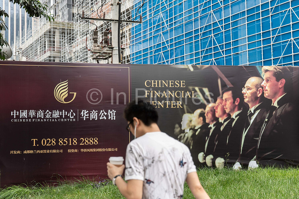 A pedestrian walks past a billboard advert for residential housing featuring western butlers in Chengdu, China, on Monday, Sept. 19, 2016. China faces unprecedented challenges as it restructures its economy away from old-line heavy manufacturing and toward consumption and services.