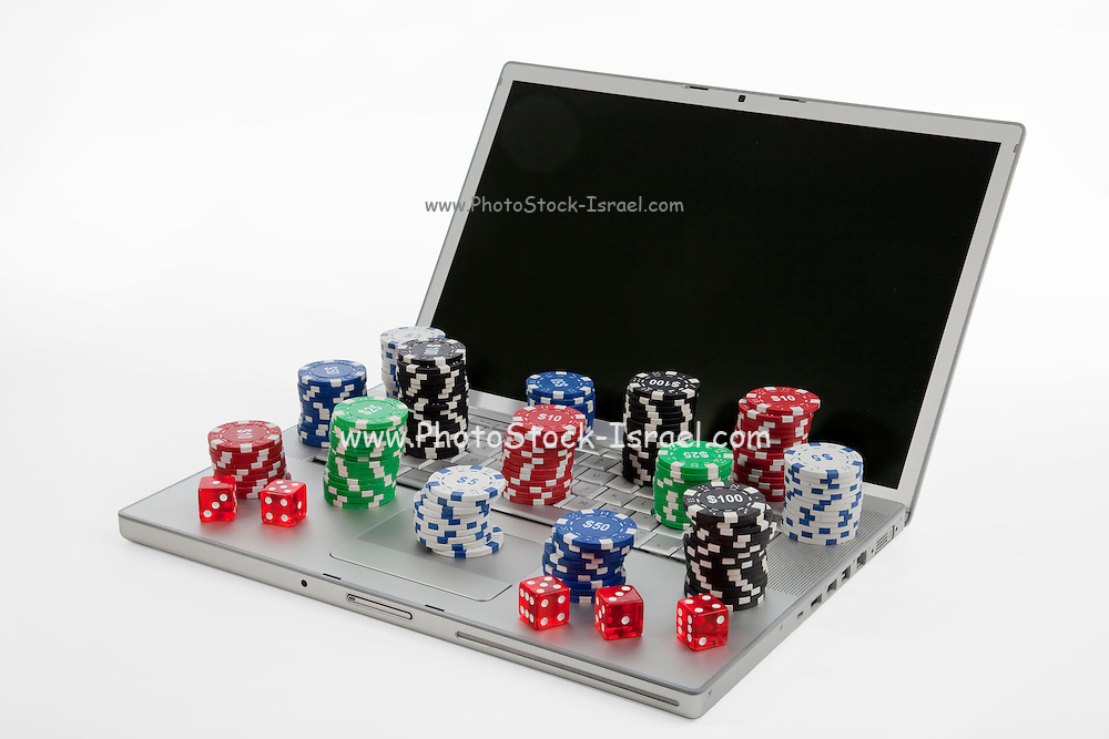 Conceptual image of on-line gambling a lap top computer with gambling chips and dice on white background