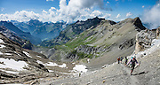 Hohtürli Pass. Above the beautiful lake of Oeschinnensee, easily reached by lift from Kandersteg, is a challenging hike traversing steeply up over Hohtürli Pass then down to Griesalp in the remote valley of Kiental, Switzerland, Europe. Ascend 1120 meters and descend 1380 m in 13 km, which feels much longer due to steep, exposed rocky & gravelly slopes. Stairs and ladders assist your footing. Optionally stay overnight in Blüemlisalp hut at Hohtürli Pass. This image was stitched from multiple overlapping photos.