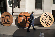 Men rolling large dining tables following an event at Freemasons Hall in London, England, United Kingdom. Hidden behind each table its as if they are moving themselves creating a strange street scene.