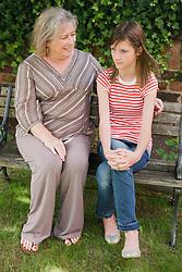 Woman and teenage girl talking on bench.