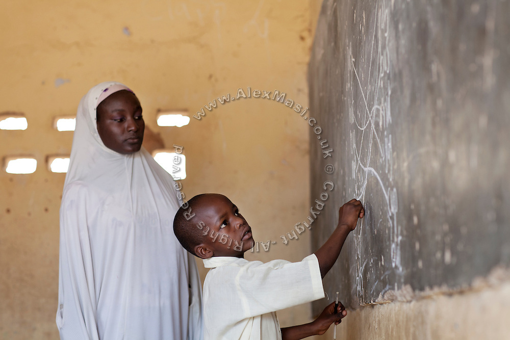 A Muslim boy is writing on the blackboard while being supervised by his teacher in Angwan Rogo government school, an institution open to pupils of any religion, but today only attended by Muslims, as it is located inside a Muslim-dominated neighbourhood where no Christian live anymore.