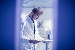 Young male scientist looking at report in an optical laboratory, Freiburg im Breisgau, Baden-W¸rttemberg, Germany