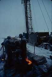 Stock photo of two men working in the snow at an on-shore rig site
