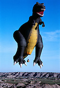 A 129-foot-tall (39 m) T.rex hot-air balloon, owned by Thunder and Colt Balloons, glides over Dinosaur Provincial Park.