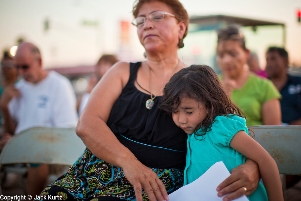 11 JULY 2010 - PHOENIX, AZ: Leticia Ruiz and her daughter, Maggie Ruiz, 3, pray the rosary on a street corner in Phoenix Sunday night. About 40 people gather nightly at an intersection in an immigrants' neighborhood in Phoenix to pray the rosary in opposition to Arizona SB 1070, a law that requires local police to question the immigration status of people they have probably cause to believe might be in the US illegally. Probable cause can include a traffic stop like speeding or having a cracked windshield. The law is being challenged in federal courts by several parties, including the US Department of Justice, which claims the law is unconstitutional because only the federal government can enact and enforce immigration laws.      PHOTO BY JACK KURTZ