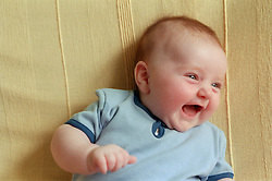 Portrait of baby lying on sofa laughing,