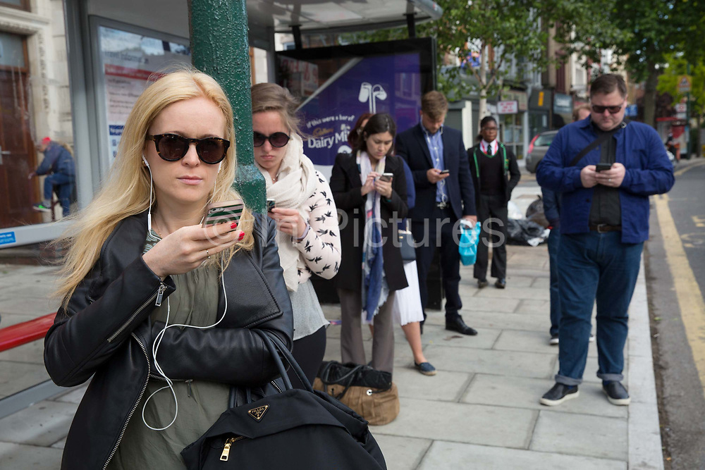 Commuters on Norwood Road check their mobile phones whilst waiting for the bus on 07th June 2017 in London, United Kingdom. From the series Our Small World, an observation of our mobile phone obsessions