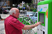 Israel, Tel Aviv, Municipal bicycle rental service now available to all residents and visitors. Man rents a bike at the touch screen post