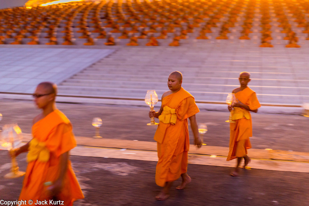 """14 FEBRUARY 2014 - KHLONG LUANG, PATHUM THANI, THAILAND:  Buddhist monks file out of the Maha Dhammakaya Cetiya during Makha Bucha Day at Wat Phra Dhammakaya. The aims of Makha Bucha Day are: not to commit any kind of sins, do only good and purify one's mind. It is a public holiday in Cambodia, Laos, Myanmar and Thailand. Many people go to the temple to perform merit-making activities on Makha Bucha Day. The day marks four important events in Buddhism, which happened nine months after the Enlightenment of the Buddha in northern India; 1,250 disciples came to see the Buddha that evening without being summoned, all of them were Arhantas, Enlightened Ones, and all were ordained by the Buddha himself. The Buddha gave those Arhantas the principles of Buddhism, called """"The ovadhapatimokha"""". Those principles are:  1) To cease from all evil, 2) To do what is good, 3) To cleanse one's mind. The Buddha delivered an important sermon on that day which laid down the principles of the Buddhist teachings. In Thailand, this teaching has been dubbed the """"Heart of Buddhism."""" Wat Phra Dhammakaya is the center of the Dhammakaya Movement, a Buddhist sect founded in the 1970s and led by Phra Dhammachayo.    PHOTO BY JACK KURTZ"""