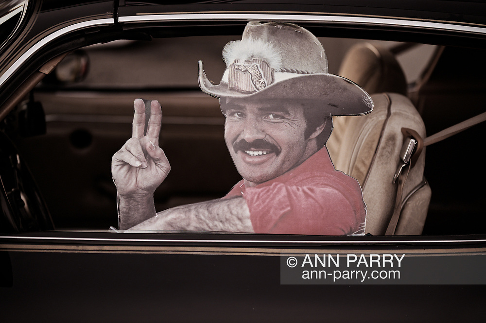 Bellmore, NY, USA. July 30, 2021. Cardboard cutout of movie star Burt Reynolds, holding up fingers making 'V for Victory' sign, is at driver's window of 1981 Pontiac Trans Am Turbo 4.8 at the Bellmore Friday Night Car Show.